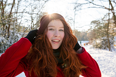 Smiling woman with hands in hair during winter - p300m2287628 by Frank van Delft