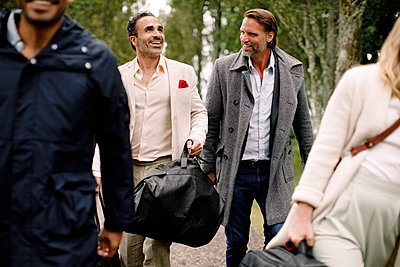 Smiling male professionals walking with colleagues during business trip - p426m2135403 by Maskot