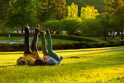Two young women lying with legs in the air in park - p429m824432 by Florin Prunoiu