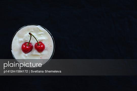 Zwei  rote Kirschen auf einem Milchshake - p1412m1584172 von Svetlana Shemeleva