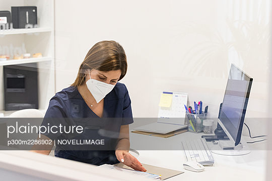 Barcelona, Spain. Woman receiving dental treatment. Clinic, cooperation, group of people, examination, female doctor, dentist, doctor, dental surgery, indoors, protective clothing, sterile, tooth, afro hair, support, healthcare, health, medicine, dental i - p300m2286902 von NOVELLIMAGE