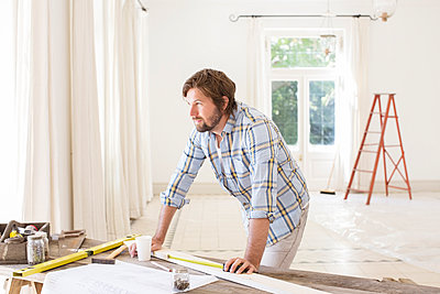 Man overlooking construction table in living space  - p1023m962417f von Martin Barraud