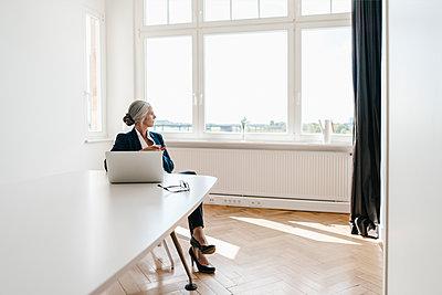 Businesswoman working on laptop in office - p300m1469656 by Kniel Synnatzschke