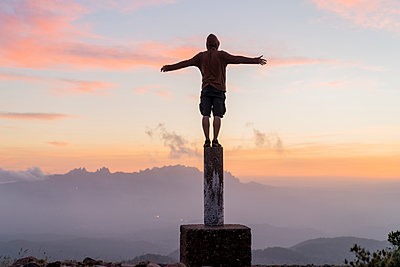 Spain, Barcelona, Natural Park of Sant Llorenc, man standing on pole at sunset - p300m2058588 von VITTA GALLERY