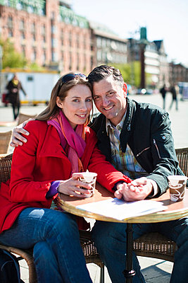 Portrait of couple drinking at outdoor cafe in city - p31225421f by Plattform photography