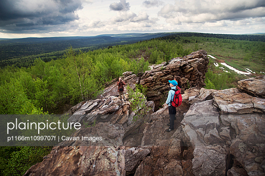 High angle view of hikers standing on rock formation - p1166m1099707f by Cavan Images