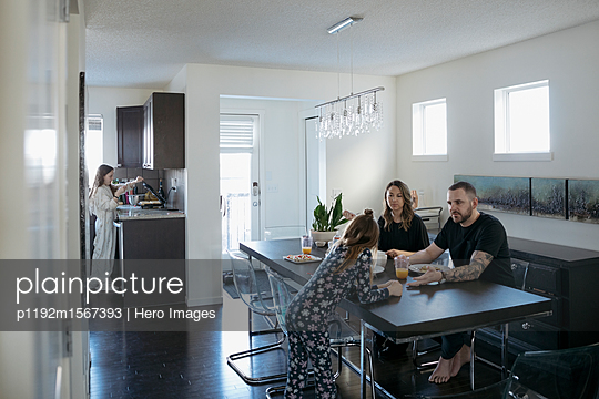 Family eating breakfast at dining table - p1192m1567393 by Hero Images