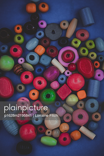 Coloured beads on plain coloured background - p1628m2195841 by Lorraine Fitch