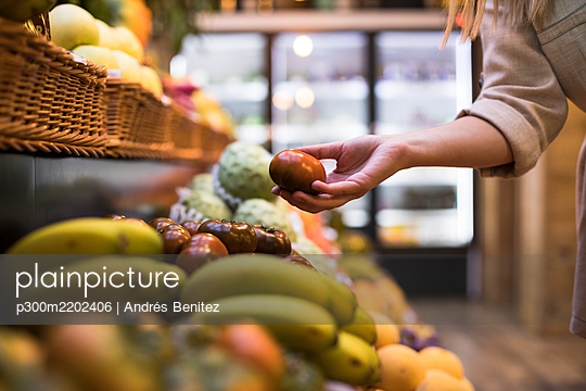 Cropped image of woman buying tomatoes at grocery store - p300m2202406 by Andrés Benitez