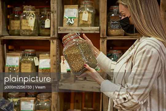 Woman with protective face mask holding spice jar at store - p300m2256733 by Veam