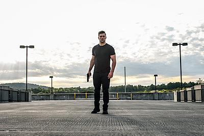 Mann mit Waffe auf einem Parkdeck - p1019m1424619 von Stephen Carroll
