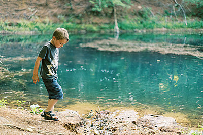 A five year old boy playing by a turquoise pond in the woods - p1166m2205700 by Cavan Images