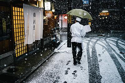 Japanischer Koch liefert frische Speisen bei starkem Schneefall aus - p1180m1446104 von chillagano