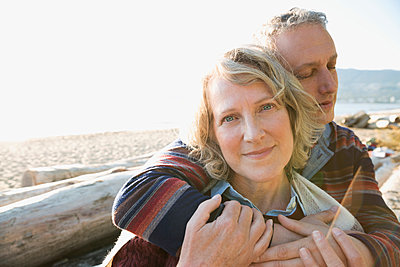 Close up serene couple hugging on sunny beach - p1192m1149468 by Hero Images