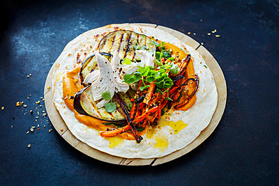 Pulled Chicken Wrap, carrot, grilled aubergine, curry hummus and herbs on chopping board - p300m1568191 by Kai Schwabe