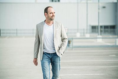 Confident mature businessman walking on parking deck - p300m2144752 by Uwe Umstätter