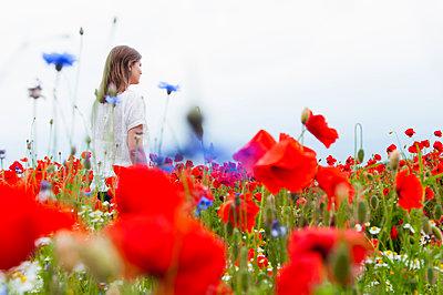 Woman walking amidst red poppy flowers on field against sky - p300m2197768 by Daniel Ingold