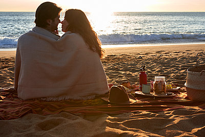 Couple covered in blanket rubbing nose while sitting on beach - p300m2244205 by Veam