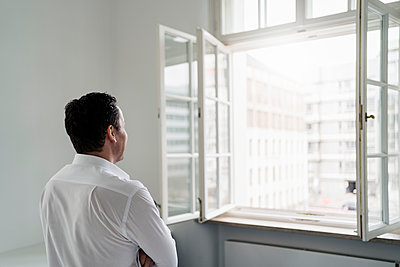 Male professional looking through window at office - p300m2274085 by Daniel Ingold