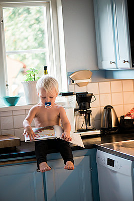 Boy with book sitting on worktop - p312m1570802 by Rebecca Wallin