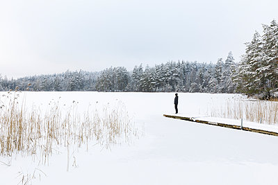Mature woman standing over frozen lake in Ostergotland, Sweden - p352m2120043 by Åke Nyqvist