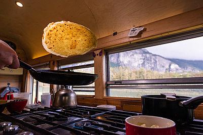 Man making pancake inside motorhome, Squamish, British Columbia, Canada - p924m2145307 by Alex Eggermont
