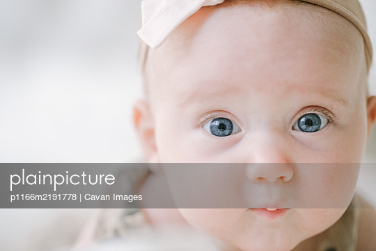 Closeup of blue eyed baby girl looking at camera - p1166m2191778 by Cavan Images