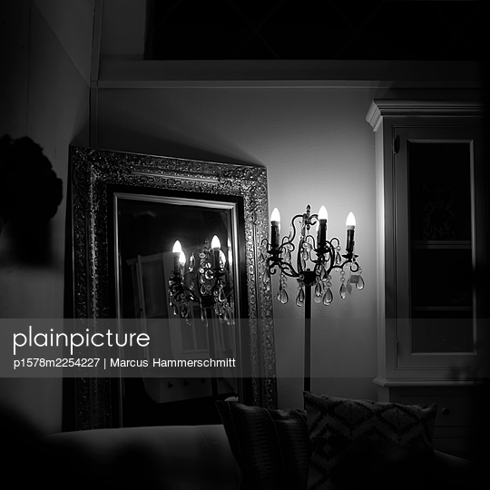 Electric candlestick in front of classy mirror - p1578m2254227 by Marcus Hammerschmitt