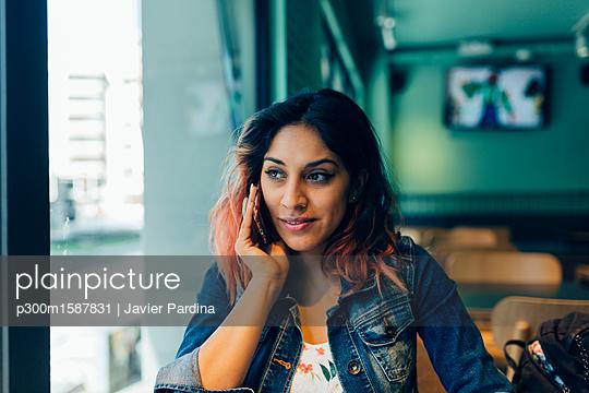 Portrait of woman on the phone in coffee shop - p300m1587831 von Javier Pardina