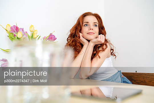 Thoughtful redhead mid adult woman sitting with hands on chin while leaning on table at home - p300m2274347 by Dirk Moll