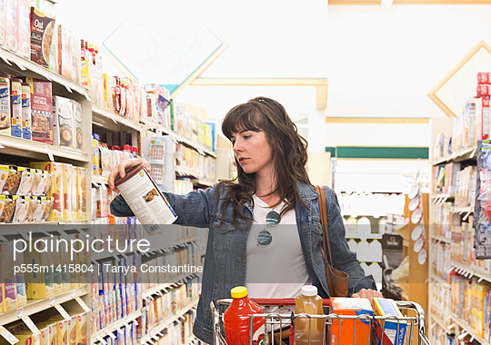 Caucasian woman shopping for groceries in store - p555m1415804 by Tanya Constantine