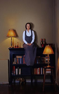 Frau sitzt auf einem Bücherregal - p1577m2150331 von zhenikeyev