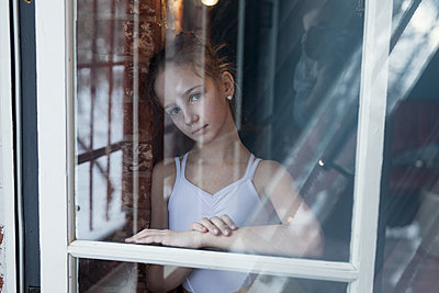 Little girl as ballerina stands at the window - p1642m2253312 by V-fokuse