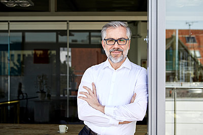 Portrait of smiling businessman standing at French door - p300m2012959 by Rainer Berg
