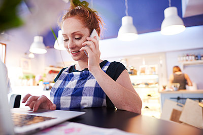 Smiling young woman working in a cafe using laptop and cell phone - p300m2023654 by gpointstudio