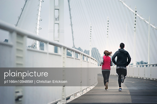 Rear view of athletes running on Bay Bridge against sky