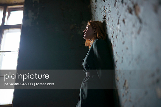 Sad teenage girl with red hair in the staircase - p1646m2245093 by Slava Chistyakov