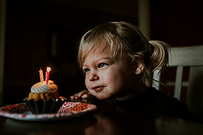 Cute girl looking at her birthday cake on table - p1166m1543908 by Cavan Images