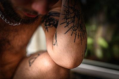 Man resting tattooed arm on his knee - p1267m2258794 by Jörg Meier