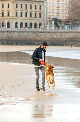 Spain, Gijon, man playing on the beach with his dog - p300m1130034f von Marco Govel