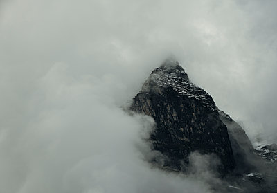 The top of the Eiger Mountain hardly visible, clouds constantly being formed around the mountain tops, Grindelwald, Bern, Switzerland - p429m2217827 by Mischa Keijser