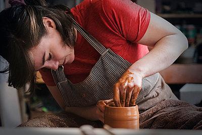 Caucasian woman shaping pottery clay - p555m1481947 by JGI/Jamie Grill