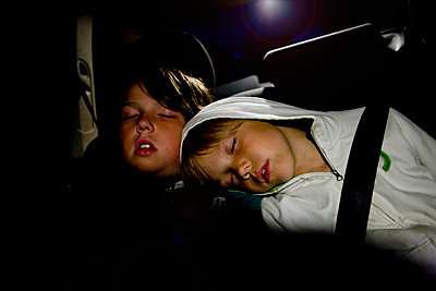 Zwei Kinder schlafen im Auto - p972m1088579 von Berno Hjälmrud