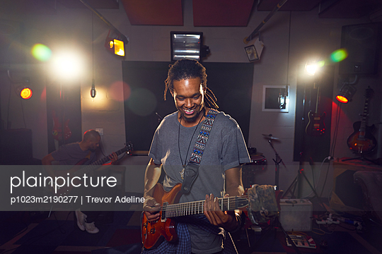Male musician playing guitar in recording studio - p1023m2190277 by Trevor Adeline