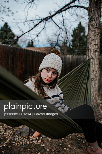 Teen girl sitting on hammock in backyard - p1166m2201314 by Cavan Images