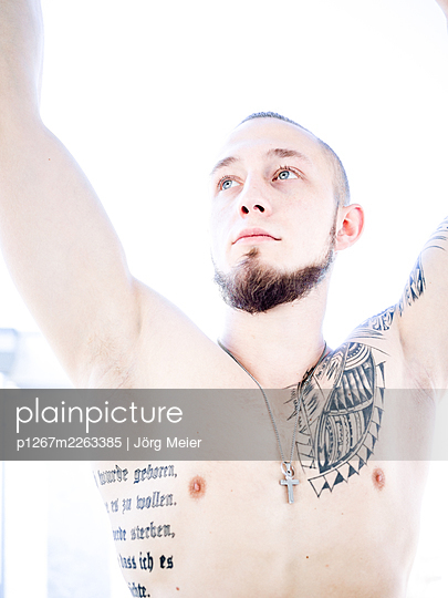 Young man with tattoos on bare chest - p1267m2263385 by Jörg Meier