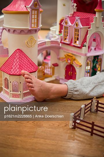 Foot in front of toy castle - p1621m2228865 by Anke Doerschlen