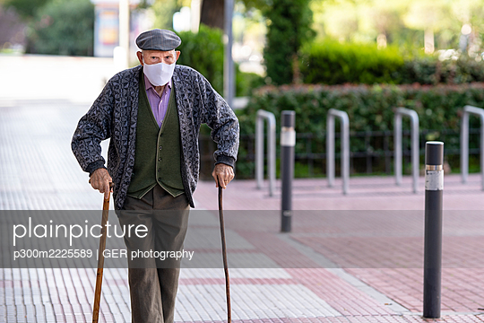 Senior man wearing protective face mask walking on footpath during COVID-19 - p300m2225589 by GER photography