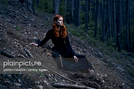 Caucasian woman sitting on hill - p555m1504224 by Dmitry Ageev