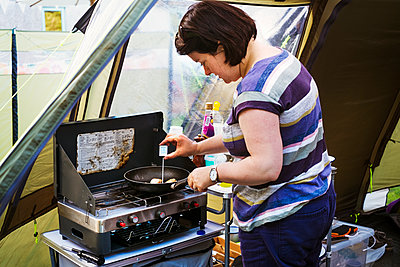 Woman standing at a camping stove, measuring the temperature of a scallop in a frying pan with a digital thermometer. - p1100m1178004 by Mint Images